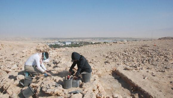Fotografie der Ausgrabungen auf dem Hügel bei Yotvata. Zwei Archäologen legen einen Befund frei.
