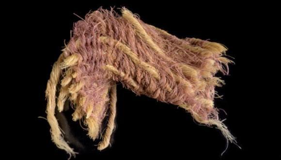 Fotografie des Textilfragments, das mit Hilfe von Fäden gefärbt in Purpur gewebt wurde. Bei den gefärbten Fäden handelt sich um die Kettfäden.