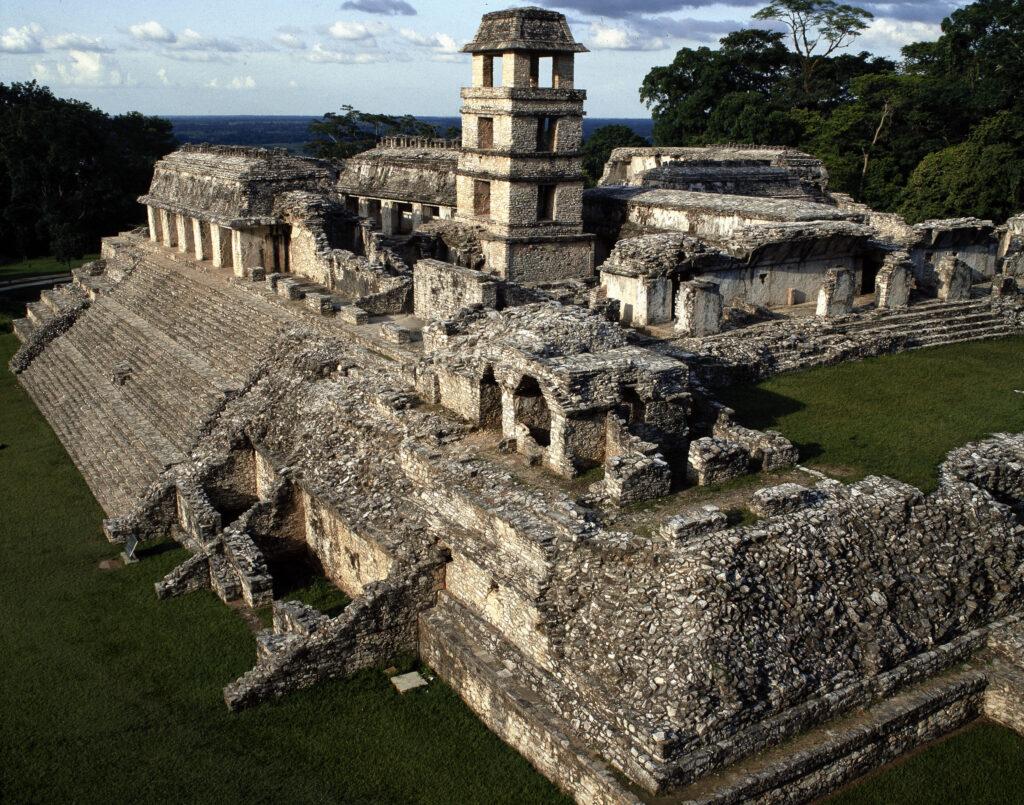 Nicht nur einfache Maya-Häuser, sondern auch Paläste wurden untersucht. Das Bild zeigt eine Fotografie des Palastareals von Palenque: Der Palast wurde auf einer hohen Terrasse gebaut und bestand aus mehreren Gebäuden, die zum Teil noch fast komplett erhalten sind. Zu sehen ist zudem ein hoher Turm, der ebenfalls noch vollständig erhalten ist.