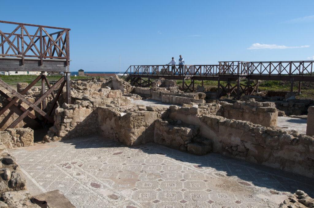 Blick auf einen rechteckigen Mosaikfußboden im Archäologischen Park von Paphos. Der Fußboden ist von aufragenden Mauerresten umgeben. Besucher können die Funde von höhergelegten Stegen aus betrachten.