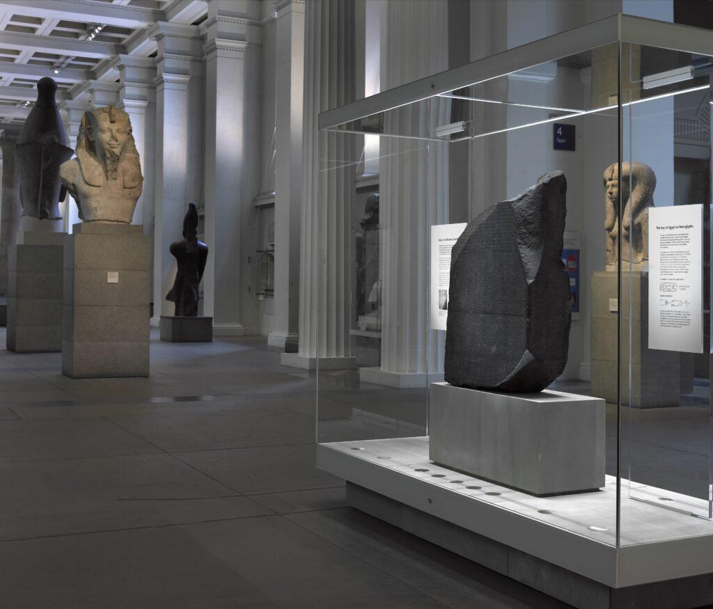 Blick in einen der Ausstellungsräume der Sammlung im Britischen Museum. Im Vordergrund ist der Stein von Rosetta zu sehen, im Hintergrund eine kolossale Büste eines Pharaos.