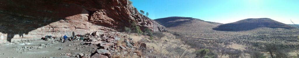 Panoramaaufnahme des Felsvorsprungs in Afrika, auf dem die Ausgrabung und die Funde für die Belege über den weiteren Ursprung des Homo sapiens gefunden wurde. Der Felsvorsprung erstreckt sich vom linken Bildrand aus bis knapp in die Mitte des Bildes und geht in einem flach abfallenden Hang in die Wüstenlandschaft der Kalahari über.
