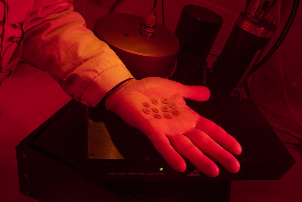 """Untersuchung der """"Miniuhren"""". Diese liegen auf dem Foto auf der Handinnenfläche einer Person, die auch die Messungen durchnimmt. Bedingt durch die Messung ist der Raum von rotem Licht erleuchtet. Die """"Miniuhren"""" sind so groß wie 1-Cent-Stücke, im Bild sind 10 Exemplare zu sehen, die zusammen und nebeneinander gelegt etwas kleiner wie ein Ei sind."""