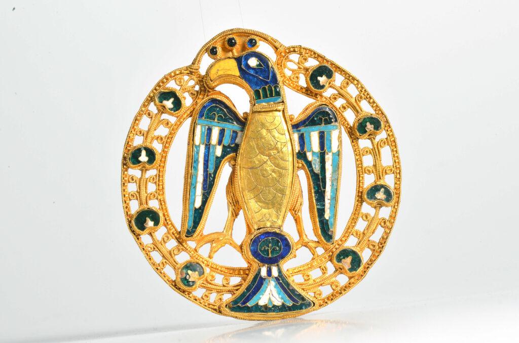 Ein Highlight der Landesausstellung: Die Große Adler-/Pfauenfibel zeigt einen stilisierten Vogel. Der Kopf ist im Profil dargestellt, die ausgebreiteten Flügel, der Körper, die Schwanzfedern und die Beine in Frontalansicht. Sowohl der Kopf, als auch die Federn bestehen aus weißen und blauen Intarsien. Der Körper und der Schnabel bestehen aus Gold. Eingerahmt wird der Adler von einem goldenen Ring, der stilisierte Blumen aufweist, deren Blütenblätter ebenfalls in Blautönen gestaltet sind.