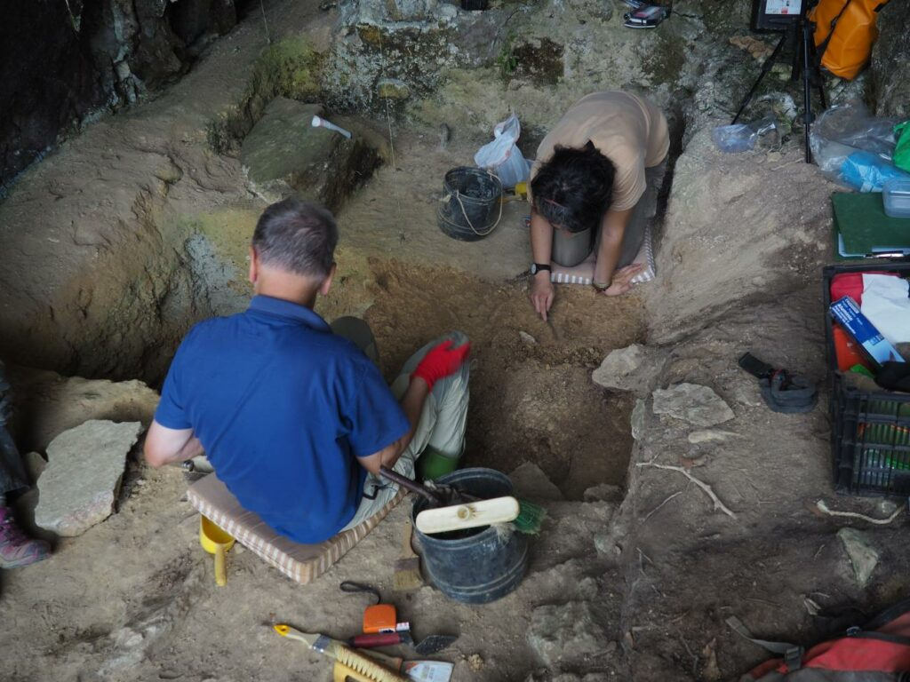 Siedlungsmuster im Paläolithikum. Zu sehen sind Ausgräber bei einer Ausgrabung eines paläolithischen Fundplatzes in einer Höhle.