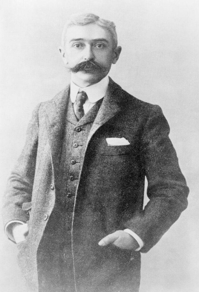 Schwarz-weiß Fotografie von Baron de Coubertin. Er blickt direkt in die Kamera und hat die Hände in die Taschen seines Jackets gesteckt. Neben einer farblich passenden Hose trägt er zudem eine Este, ein weißes Hemd und eine Krawatte. Die Haare sind in einen leichten Seitenscheitel gelegt.