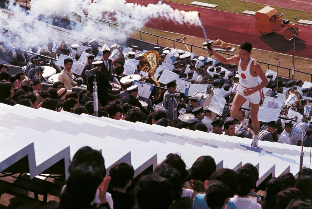 Japanischer Fackelläufer während der Olympischen Spiele in Tokio. Der Mann läuft die weißen Stufen zur Feuerschale empor. In seiner rechten Hand hält er die Fackel. Er trägt ein weißes Sporttop mit einem roten Kreis, die Farben von Japan, und eine kurze Sporthose. Links und rechts der Stufen sitzen die Zuschauer.