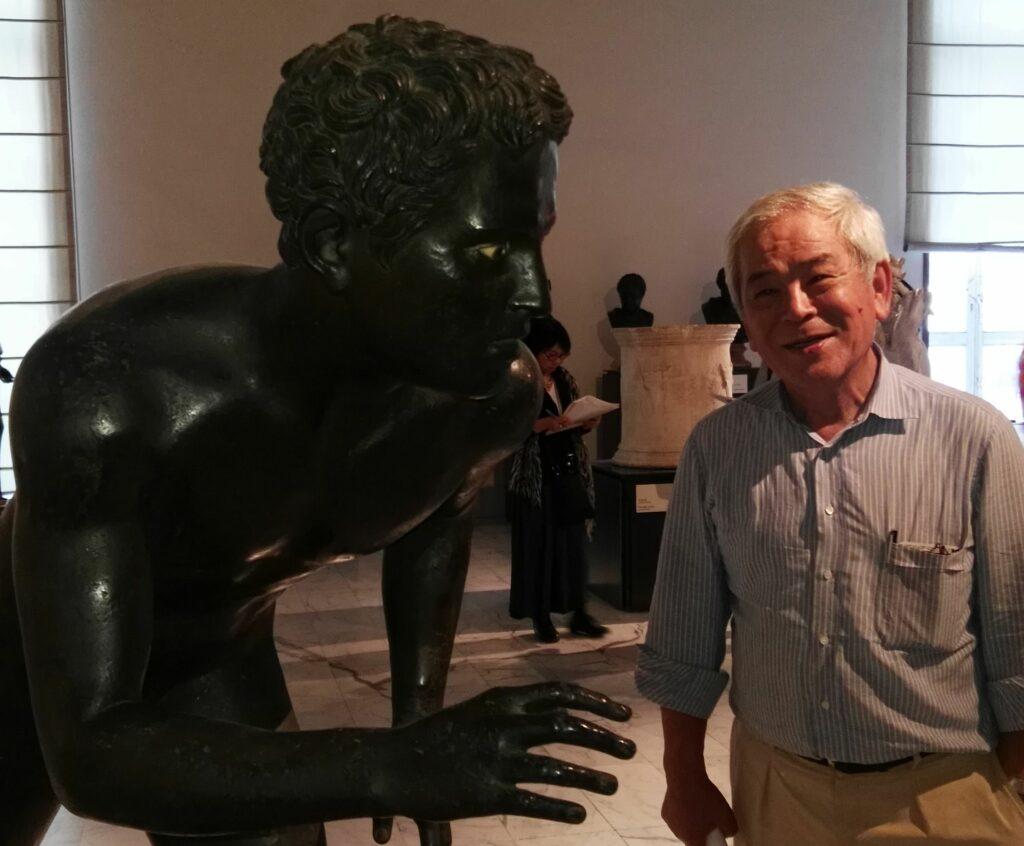 Foto von Masanori Aoyagi neben einer Statue aus Bronze.
