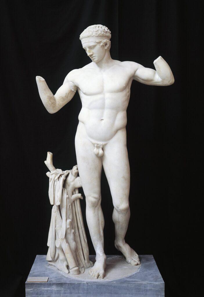 Diadumenos des Polyklet, der sinnbildlich für die Sieger der Olympischen Spiele gesehen werden kann. Männlicher Akt aus weißem Marmor in kontrapostischer Haltung: das linke Bein ist das Spielbein, das rechte das Standbein. Die Arme gehen zum Kopf. Dieser ist leicht nach vorne geneigt. Der Mann ist im Begriff, sich eine Siegerbinde umzubinden (als Band am Kopf erhalten).