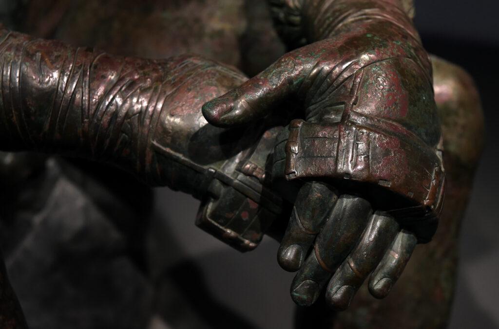 Detailaufnahme der Boxhandschuhe eines Faustkämpfers. Um den Handrücken sind dünne Bänder gewickelt, die Finger werden zur Hälfte (zur Hand hin) von einem dicken Riemen geschützt. Die vorderen Fingerglieder sind ungeschützt. Die Statue verdeutlicht, wie die antiken Boxhandschuhe zur Zeit der Olympischen Spiele ausgesehen haben könnten.
