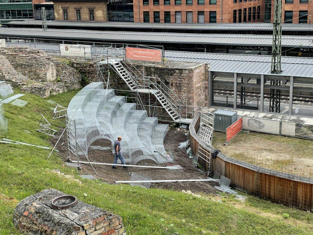 Das Foto zeigt einen Teil der bereits aufgebauten Sitzkulissen im Römischen Theater in Mainz. Insgesamt sieben Sitzreihen sind zu sehen, von denen zwei jeweils eine tonnenartige Struktur als Unterbau aufweisen.