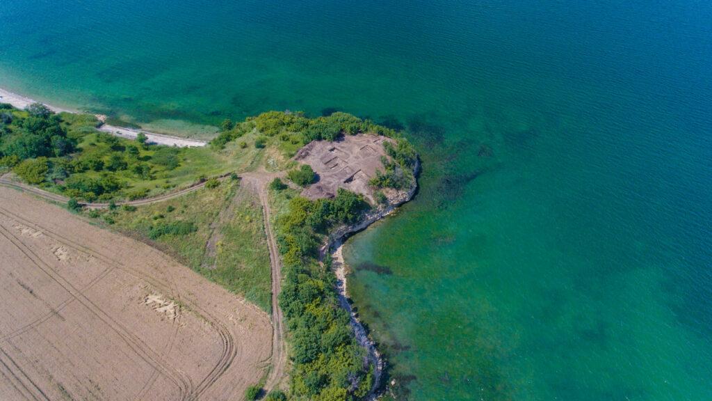 Die Aufnahme zeigt das Kap Chiroza auf dem sich die Ausgrabungsstätte befindet.  Die Stätte selbst befindet sich auf einem Landvorsprung direkt am Wasser und ist auf zwei Feldwegen zu erreichen, die an einem Acker vorbeiführen.