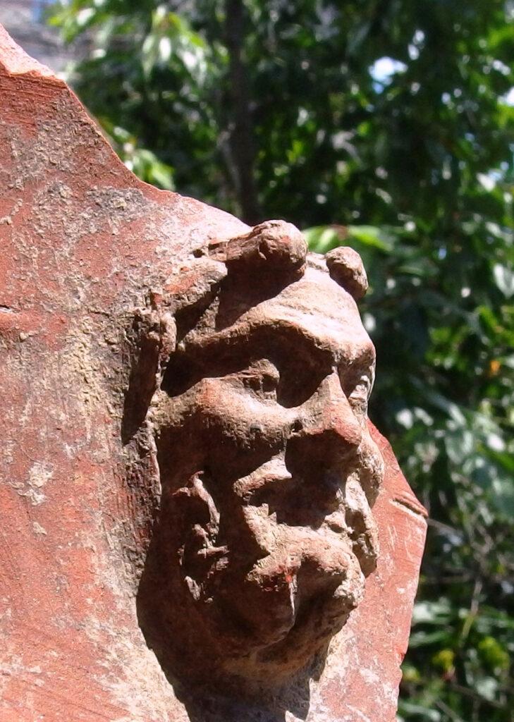 Die Scherbe besteht aus einem rötlichen Ton. Auf der Scherbe sitzt ein männlicher Kopf. Dieser hat die Augen geschlossen und trägt einen Vollbart. Um die Stirn ist der Ansatz eines Kranzes zu erkennen.