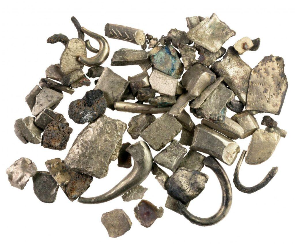 Das Bild zeigt einen Hortfund bestehend aus Hacksilber, das für den Silberhandel verwendet wurde. Dieses besteht aus mehreren unterschiedlichen geformten Silberstücken, darunter dünne Metallplättchen und Fragmente von Ringen oder Henkeln.