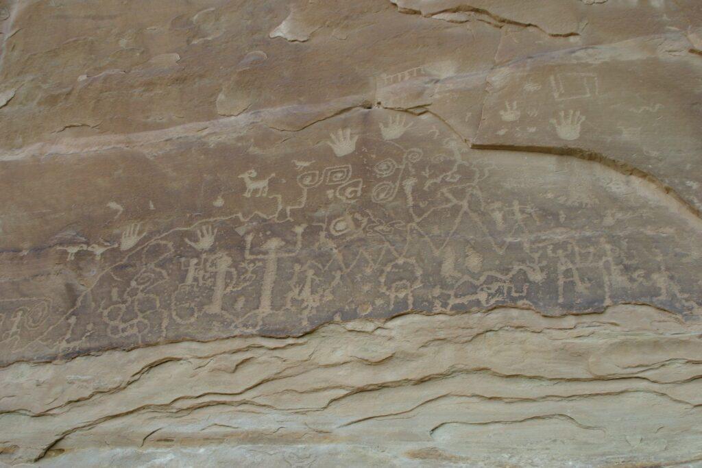 Das Foto zeigt Petroglyphen. Der Felslack wird als schwarze Verfärbung auf dem Gestein sichtbar. Zu sehen sind anthropomorphe und abstrakte, geometrische Darstellungen, sowie Darstellungen von Tieren (Vögel, Cerviden) und Handabdrücke.