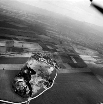 Schwarz-weiße Luftbildaufnahme von Alalakh. Der Fundort befindet sich in Mitten von Feldern und Ackerfläche.