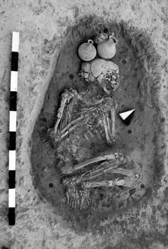 Hockerbestattung eines Toten in Alalakh. Die Person ist mit Blickrichtung nach rechts platziert, die Beine liegen eng am Körper an und die Arme sind vor der Brust gefaltet. Der Kopf ist zur Seite gedreht. Über dem Kopf  wurden zwei dickbäuchige Tonkrüge platziert.