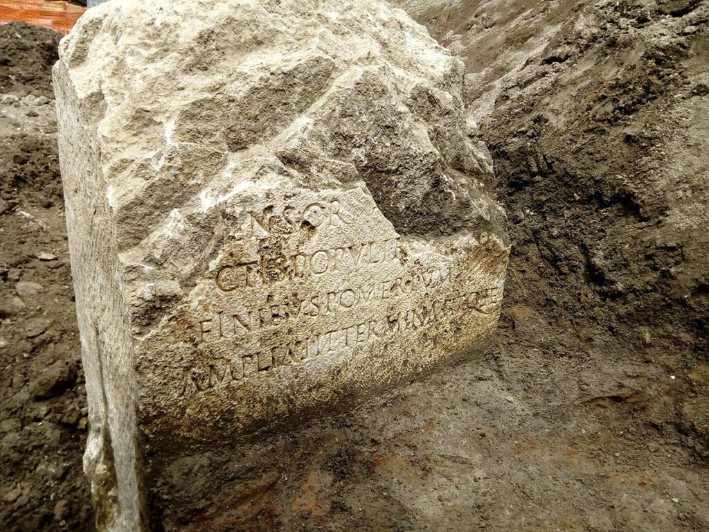Das Foto zeigt die gesäuberte Inschrift in Fundlage. Der obere Teil des Steins ist abgebrochen. In der zweitletzten Zeile verweisen die Worte FINIBUS POMERIUM auf die Erweiterung des Pomeriums hin.