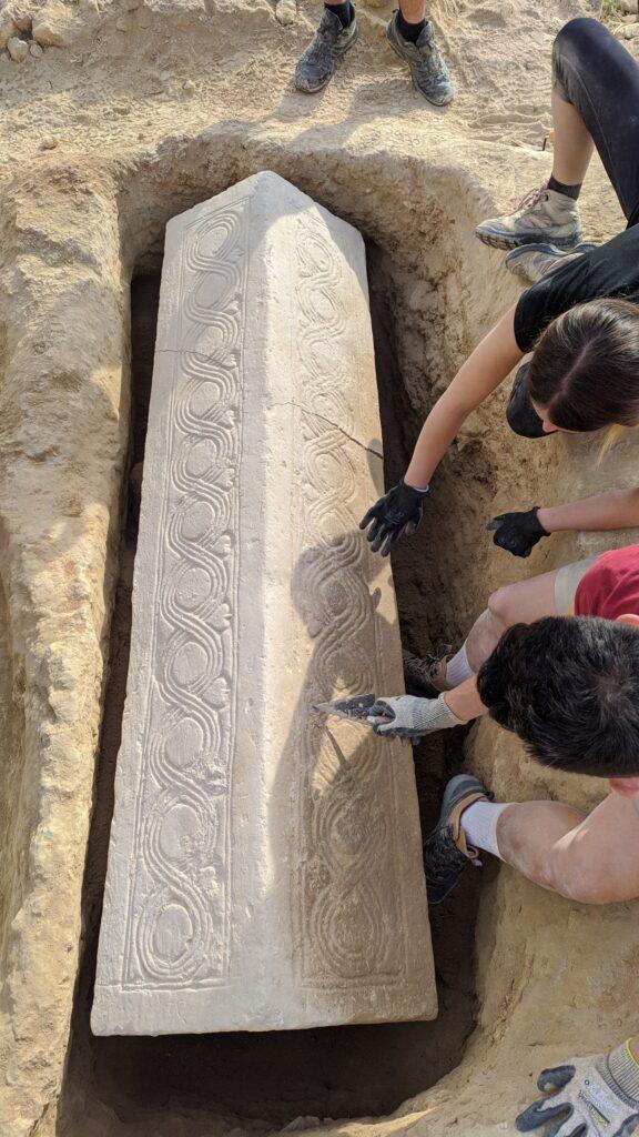 Die Fotografie zeigt den freigelegten Sarkophag. Dieser wurde aus einem weißlichen Stein gefertigt. Auf dem Deckel ist ein sich wiederholendes Rankenmuster zu sehen. Der Deckel ist zudem wie ein Satteldach geformt.