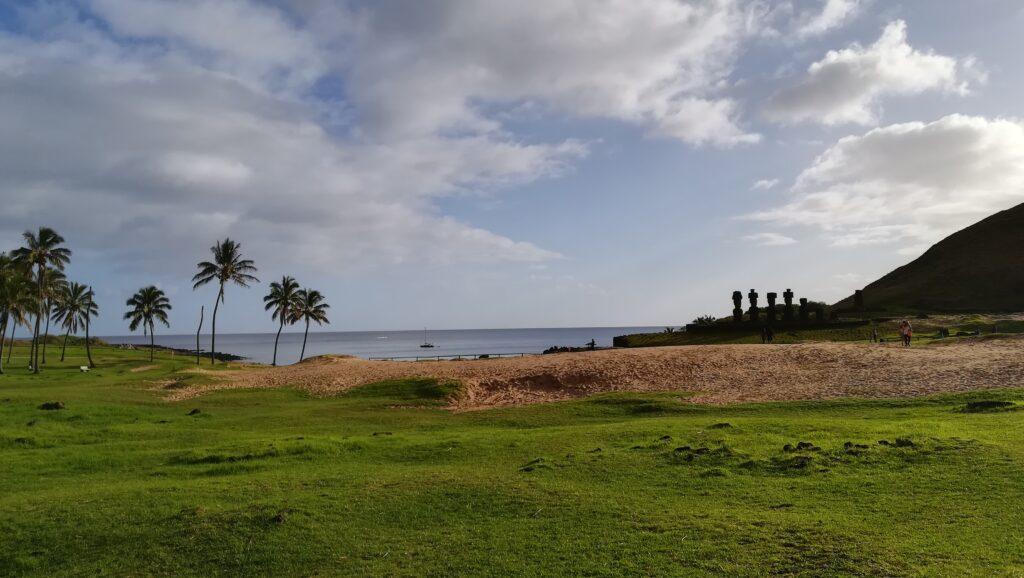 Das Bild zeigt den Anakena Beach von Rapa Nui. Zu sehen ist im Hintergrund das Meer, auf dem ein Boot schwimmt. Im Vordergrund befindet sich eine Graslandschaft, die ab der Bildmitte in den Strand übergeht. Am linken Bildrand stehen vereinzelt Palmen und am rechten Bildrand beginnt ein Hügel, an dessen Fuß sich Moai-Statuen befinden.