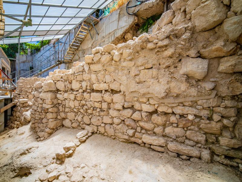 Das Bild zeigt den freigelegten Abschnitt der Stadtmauer. Die Mauer selbst besteht aus unregelmäßig großen quaderförmigen Steinen.