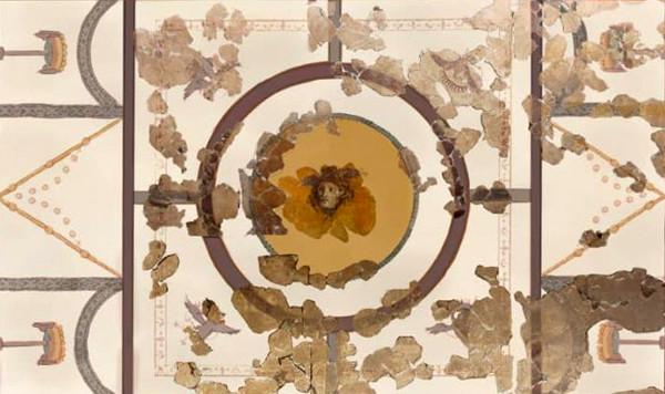 Das Bild zeigt die Freskendecke aus der Villa San Marco, deren Restaurierung mit Hilfe einer Crowdfunding-Kampagne realisiert werden soll. Die Decke ist mit Hilfe von zwei dicken farbigen Balken in drei Abschnitte gegliedert, wobei die beiden äußeren Abschnitte gleichgroß aber kleiner als der mittlere Abschnitt sind. Zudem weisen sie das gleiche Dekor auf. Jeder der beiden äußeren Abschnitte ist in noch einmal waagerecht in drei Segmente geteilt. Die beiden äußeren Segmente zeigen jeweils das gleiche Objekt: Ein halbrundes Objekt, an dessen Öffnung kugelrunde Applikationen angebracht sind, steht auf einem langen Ständer, der in einen schmalen Fuß mündet. Eingerahmt wird das Objekt jeweils von einem aufgemalten Dekor, das an einen stilisierten Vorhang erinnert. Im mittleren Segment befindet sich ein aufgemaltes v-förmiges Dekor. Der mittlere Abschnitt der Decke wird von einem runden Medaillon dominiert, das fast den gesamten Abschnitt einnimmt. Das Medaillon zeigt ein Gesicht, das von wallenden Haaren und einem Kopfschmuck, vielleicht ein Flügelpaar, gerahmt wird. Um das Medaillon herum verläuft ein rechteckiger Dekor in dessen Zwickeln sich Vögel befinden, die sich auf das Medaillon zu bewegen scheinen. Bei der Aufnahme handelt es sich um eine Rekonstruktion der Decke, die teilweise mit den originalen Fragmenten ergänzt wurde.