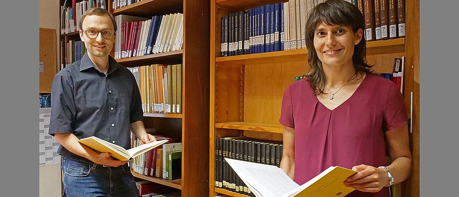 Digitalisierungsschub für die Altertumswissenschaften: Auf dem Foto sind Holger Essler und Birgit Breuer zu sehen. Beide stehen vor einem Regal mit Büchern und schauen direkt lächelnd in die Kamera. Außerdem halten beide jeweils ein aufgeschlagenes Buch (mit gelbem Einband) in den Händen.