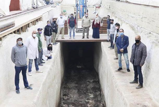 Das Bild zeigt das archäologische Team an der Grube des zweiten Khufu-Boots. Alle stehen um die Grube herum und schauen in die Kamera. Die Grube selbst ist tief in den weißen Steinboden gegraben und zur Zeit der Aufnahme leer.