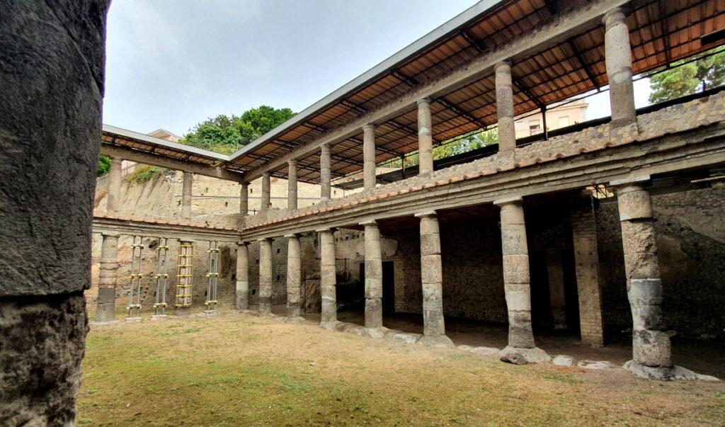 Das Foto zeigt die zweistöckige Portikusanlage der Villa B von Oplontis. Der Portikus weist eine quadratische Grundfläche auf. Zu sehen sind eine Längsseite mit angrenzenden Räumen und eine offene Stirnseite. Die dorischen Säulen des unteren Stockwerks tragen ein schmal hervorragendes Dach hinter dem sich die Säulenreihe des oberen Stockwerks erhebt. Die Säulen selbst sind kleiner als die im Erdgeschoss und stehen zusätzlich auf einer kleinen Mauer. Darüber erhebt sich, anstelle des antiken Gebälks, ein modernes Schutzdach.