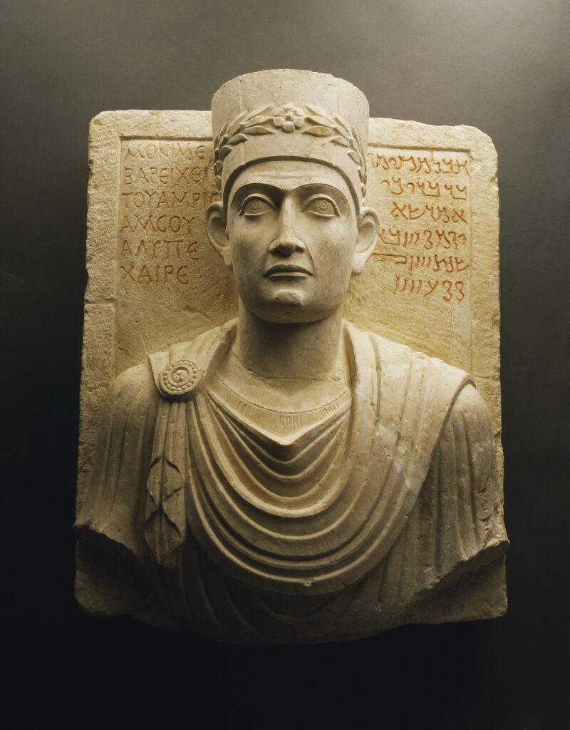 Grabrelief eines Priesters aus Palmyra mit Büste des Verstorbenen sowie der Grabinschrift auf Griechisch und Palmyrenisch; 1.–2. Jh. n. Chr.; Kalkstein; Höhe 53 cm, Breite 43 cm, Tiefe 23 cm; Palmyra Museum.