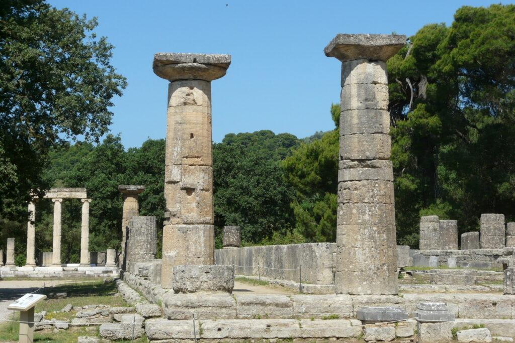 Blick in das Heiligtum von Olympia. Rechts der um 600 v. Chr. errichtete Tempel der Göttin Hera, im Hintergrund links das von Philipp II. von Makedonien gestiftete Philippeion.