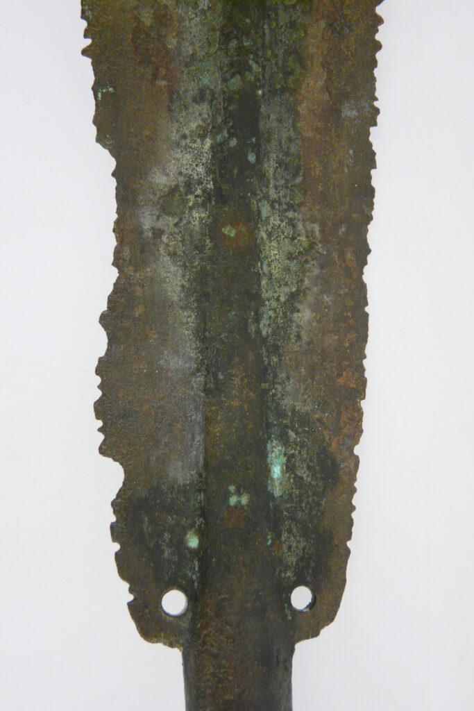 Blatt einer bronzenen Lanzenspitze mit intentional zerstörten Schneiden. Das Stück gelangte aus Sizilien nach Olympia. Weihgabe.