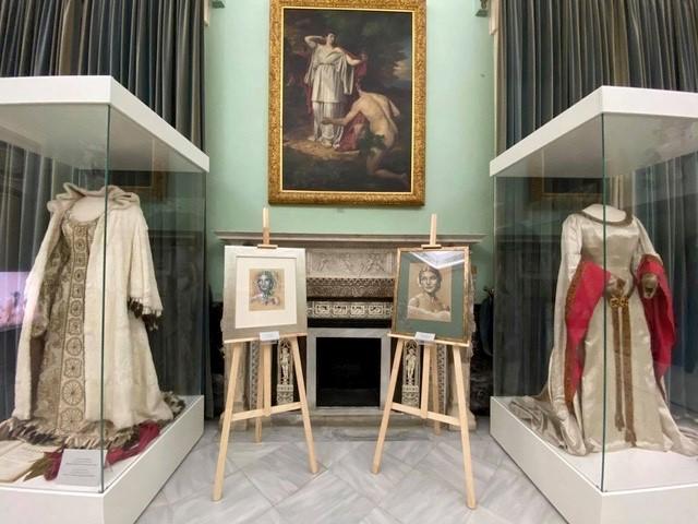 Blick in die Ausstellung. Zu sehen sind zwei Kostüme der Sängerin Maria Callas sowie zwei Porträts von ihr. Dahinter hängt an einer grünen Wand ein Bild von Nasikaa und Odysseus.