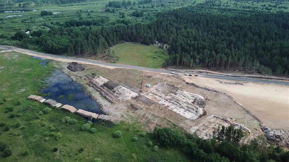 Die Luftbildaufnahme zeigt die Ausgrabungen während dem Bau der Autobahn in der Nähe des Dorfes Maloje Okulowo. Unterhalb der Straße sind drei große Flächen zu sehen, die ausgegraben werden.