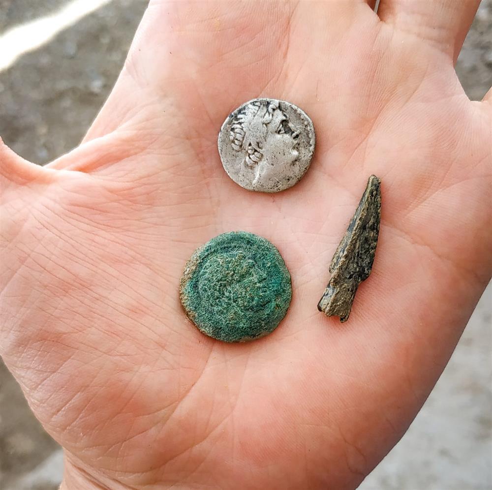 Eine Silber- und Kupfermünze von Eutidemus I. und eine bronzene Pfeilspitze.
