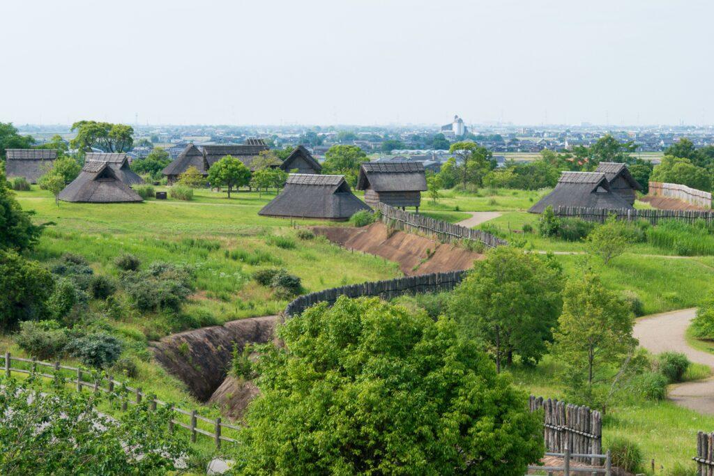 Die Stätte Yoshinogari aus der Yayoi-Zeit war mit einer für diese Zeit typischen Grabenanlage umgeben, die noch heute sichtbar ist. Zudem wurden einige der historischen Häuser wieder aufgebaut. Die Stätte war zudem mit einer hohen Pallisade aus Holz umgeben. Die Häuser stehen zum Einen auf Pfählen, zum anderen wurden sie direkt auf Fundamenten im Boden gebaut. Typisch für diese Häuser ist das Dach, das bis auf den Boden reicht.