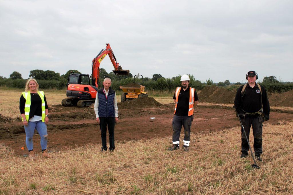 Vier Personen/Archäologen stehen vor der Grabungsfläche der Römischen Villa von Wrexham in Wales.