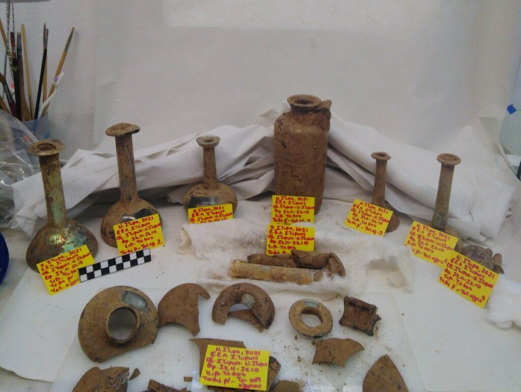 Das Bild zeigt die im Grab gefundenen Glasgefäße und Glasflaschen, die alle stark verschmutzt und zum Teil nur noch in Fragmenten erhalten sind.