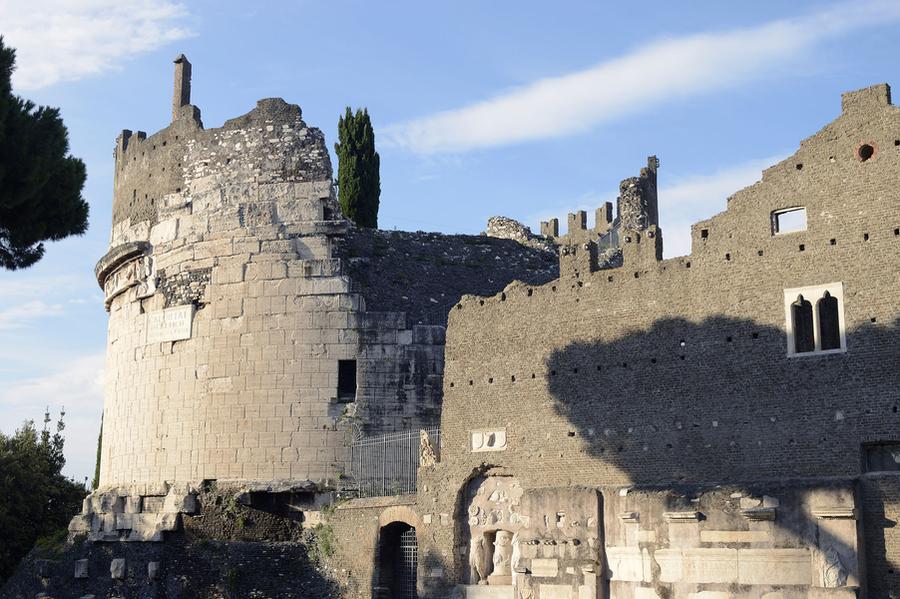Bild des Grabmals der Caecilia Metella an der Via Appia. Noch heute ist es sehr gut erhalten, lediglich der obere Abschnitt des kreisrunden Bauwerks ist zu Teil verfallen. Gut sichtbar ist noch der umlaufende Fries sowie die Inschrift. Die Zinnen, die den Abschluss des Grabmals aus Beton bilden, wurden später ergänzt.