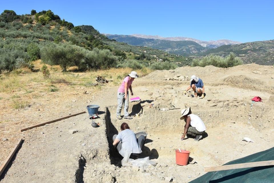 """Zu sehen sind mehrere Personen, die im Grabungsschnitt arbeiten und die Reste des Gebäudes vom Typ """"Megaron"""" freilegen."""